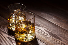 Glasses of whiskey with ice on wood Stock Photo