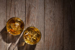 Glasses of whiskey with ice on wood Royalty Free Stock Image