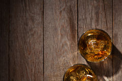 Glasses of whiskey with ice on wood Royalty Free Stock Photos