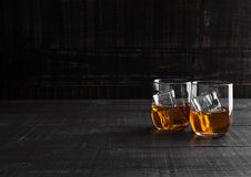 Glasses of whiskey with ice on wooden background Stock Photos