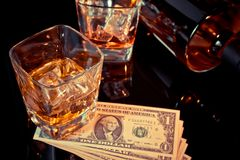 Glasses of whiskey near bottle and dollars on a black table. Western theme style Stock Image