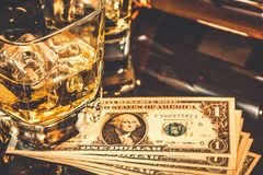 Glasses of whiskey near bottle on dollars money on a black table. Old western theme style Stock Photos