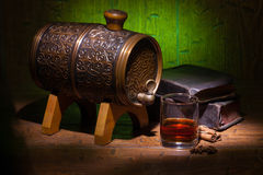 Glasses of whiskey, spicery, books and small barrel. Glasses of whiskey, books, cinnamon, star anise and small vantage barrel on old wooden table with green stock photo