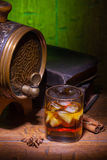 Glasses of whiskey, spicery, books and small barrel. Glasses of whiskey, books, cinnamon, star anise and small vantage barrel on old wooden table with green royalty free stock photos