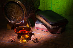 Glasses of whiskey, spicery, books and small barrel. Glasses of whiskey, books, cinnamon, star anise and small vantage barrel on old wooden table with green royalty free stock photography