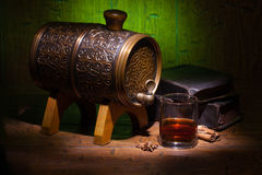 Glasses of whiskey, spicery, books and small barrel. Glasses of whiskey, books, cinnamon, star anise and small vantage barrel on old wooden table with green royalty free stock images