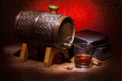 Glasses of whiskey, spicery, books and small barrel. Glasses of whiskey, books, cinnamon, star anise and small vantage barrel on old wooden table with red stock photos