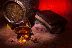 Glasses of whiskey, spicery, books and small barrel. Glasses of whiskey, books, cinnamon, star anise and small vantage barrel on old wooden table with red royalty free stock photography