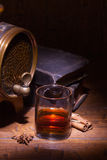 Glasses of whiskey, spicery, books and small barrel. Glasses of whiskey, books, cinnamon, star anise and small vantage barrel on old wooden table. Vintage royalty free stock photos