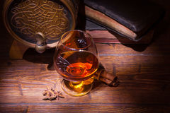 Glasses of whiskey, spicery, books and small barrel. Glasses of whiskey, books, cinnamon, star anise and small vantage barrel on old wooden table. Vintage stock photography