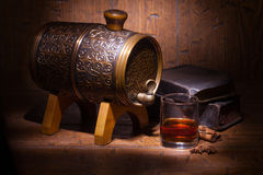 Glasses of whiskey, spicery, books and small barrel. Glasses of whiskey, books, cinnamon, star anise and small vantage barrel on old wooden table. Vintage royalty free stock image