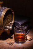 Glasses of whiskey, spicery, books and small barrel. Glasses of whiskey, books, cinnamon, star anise and small vantage barrel on old wooden table. Vintage stock photo