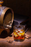 Glasses of whiskey, spicery, books and small barrel. Glasses of whiskey, books, cinnamon, star anise and small vantage barrel on old wooden table. Vintage royalty free stock images