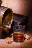 Glasses of whiskey, spicery, books and small barrel. Glasses of whiskey, books, cinnamon, star anise and small vantage barrel on old wooden table. Vintage stock image