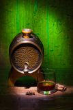 Glasses of whiskey, spicery and small barrel. Glasses of whiskey, cinnamon, star anise and small vantage barrel on old wooden table with green background stock photo
