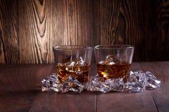 Glasses of whiskey on wood background. Ice stock photos
