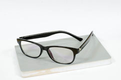 Glasses on the white book. Picture of black glasses on a white book Stock Photos