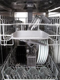 Glasses and white plates in a modern dishwasher machine Royalty Free Stock Photo