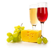 Glasses of white and red wine with cheese and grapes Stock Image