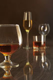Glasses with white, red wine and cognac or whisky on mirror table. Celebrities composition. Stock Photos