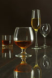 Glasses with white, red wine and cognac or whisky on mirror table. Celebrities composition. Stock Images