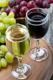 Glasses of white and red wine, fresh grapes on board Royalty Free Stock Photos