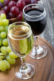 Glasses of white and red wine, fresh grapes on a wooden board Stock Images