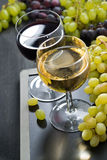 Glasses of white and red wine and grapes on a blackboard Royalty Free Stock Images