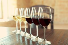 Glasses of white and red wines. On wooden table stock photos