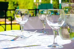 Glasses and white tablecloth on table Royalty Free Stock Image