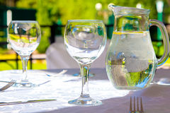 Glasses and white tablecloth on table in summer Stock Photo