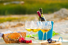 Glasses of the white wine on the beach on sunset, picnic theme, royalty free stock photo