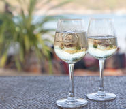 Glasses of white wine with ice on a table at the beach cafe Stock Image