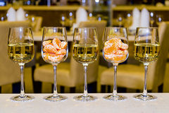 Glasses of white wine and tangerines. Glasses of white wine and tangerines in a row on a bar Royalty Free Stock Images