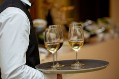 Glasses with wine on a tray. Meeting with guests. The waiter carries a tray with wine stock photography