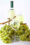 Glasses of white wine with white grapes. Glasses of white wine with bottle and grapes on white background Royalty Free Stock Photo