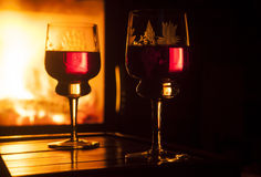 Glasses of wine against fireplace Stock Photo