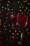 Glasses with wine. Against hearts Royalty Free Stock Photography