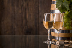 Glasses of wine with barrel and grapes. And dark background royalty free stock photos