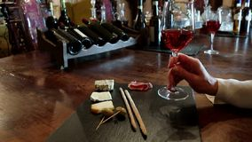 Glasses of wine and cheese plate. Wine testing. Wine test, crystal glass, red wine, cheese, bar counter background. Glasses of wine and cheese plate. Wine stock footage