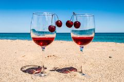 Glasses of wine and cherries near the sea Royalty Free Stock Images