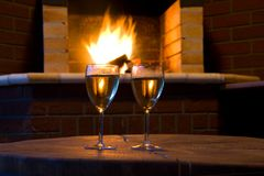 Glasses of wine in front of a fireplace Stock Photos