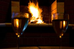 Glasses of wine in front of a fireplace Stock Images
