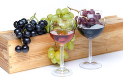 Glasses of wine in front of a wooden box with grapes Stock Photos