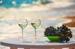 Glasses of wine and grapes on the background of the sea. Royalty Free Stock Photos