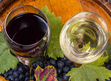 Glasses of wine and grapes on barrel Royalty Free Stock Photos