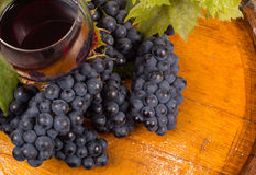 Glasses of wine and grapes on barrel.  Stock Image