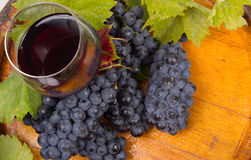 Glasses of wine and grapes on barrel Stock Photo