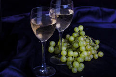 Glasses of wine and grapes on a dark background Royalty Free Stock Photo