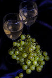 Glasses of wine and grapes on a dark background Royalty Free Stock Images